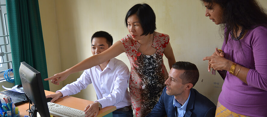 A data manager explains electronic aggregate reporting system to Hien Thu Bui, Kenneth Landgraf and Reshma Kakkar at Nam Tu Liem